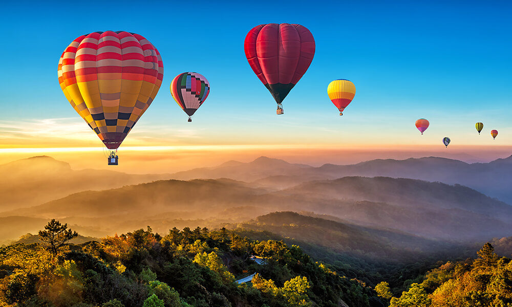 a group of a hot air balloons above mountains